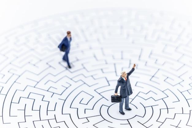Miniaturleute geschäftsmann, der auf mitte des labyrinths unter verwendung steht