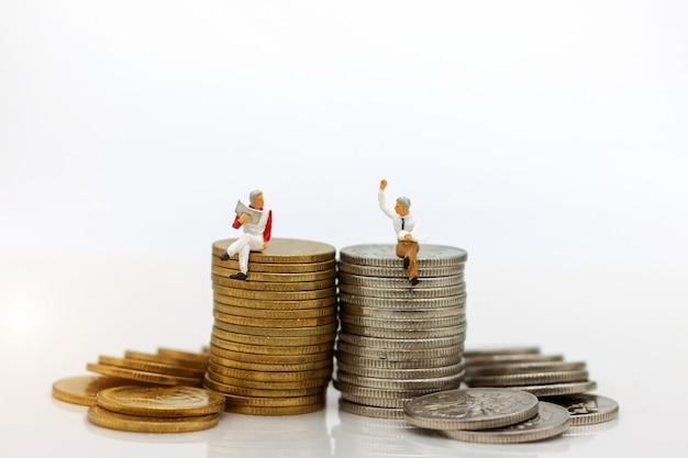 Miniaturleute: geschäftsmann, der auf münzenstapel sitzt.
