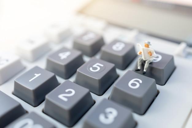 Miniaturleute: geschäftsmann, der auf taschenrechner liest. finanz- und geschäftskonzept