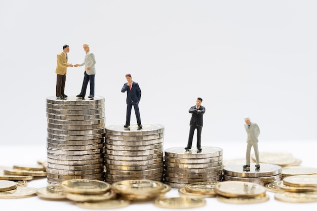 Miniaturleute: geschäftsmann, der entscheidung auf münzenstapeln trifft