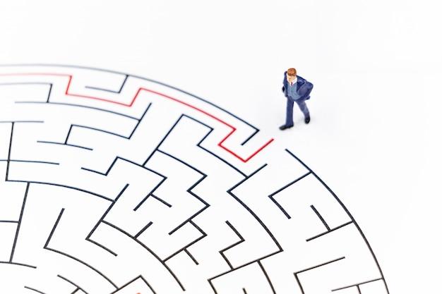 Miniaturleute geschäftsmann, der in ein labyrinth geht.