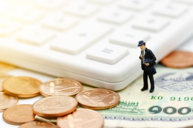 Miniaturleute: geschäftsmann, der mit taschenrechner und münzengeld steht.
