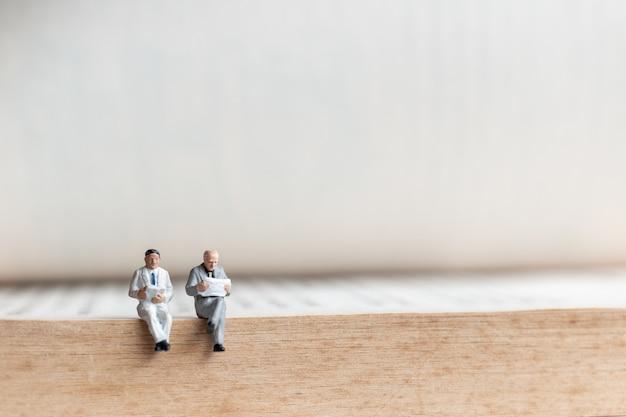Miniaturleute: geschäftsmannlesebuch auf altem buch