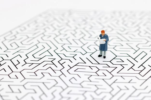 Miniaturleute: geschäftsmannlesung auf mitte des labyrinths.