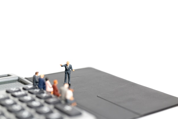 Miniaturleute: geschäftsmannsitzung auf dem rechner lokalisiert auf weißem hintergrund