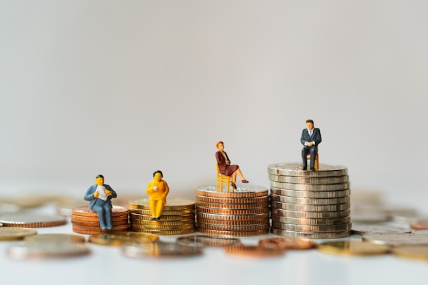 Miniaturleute, geschäftsteam, das auf stapelmünzen unter verwendung als geschäftsteamwork und finanzkonzept sitzt