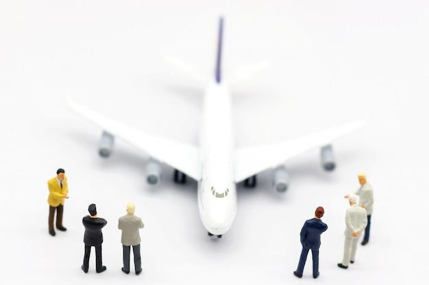 Miniaturleute: geschäftsteam, das vor flugzeug steht. unternehmenskonzept.