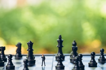 Miniaturleute Geschäftsmänner, die Schachanalyse stehen, kommunizieren