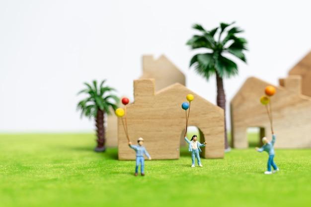 Miniaturleute: glückliche familie, die auf dem gebiet mit ballonen geht
