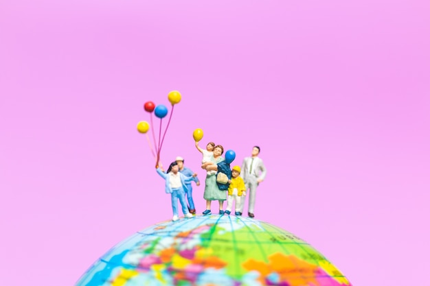 Miniaturleute: glückliche familie, die ballon auf der kugel mit rosa hintergrund hält