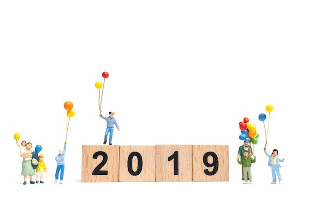 Miniaturleute: glückliche familie, die ballon auf nr. 2019 hält