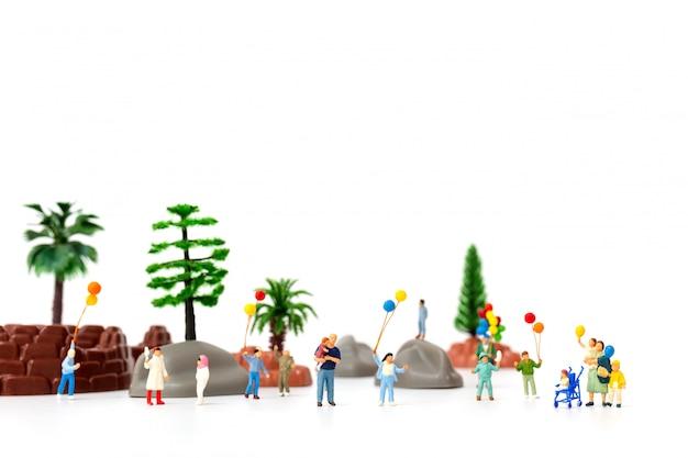 Miniaturleute: glückliche familie, die ballon im park hält
