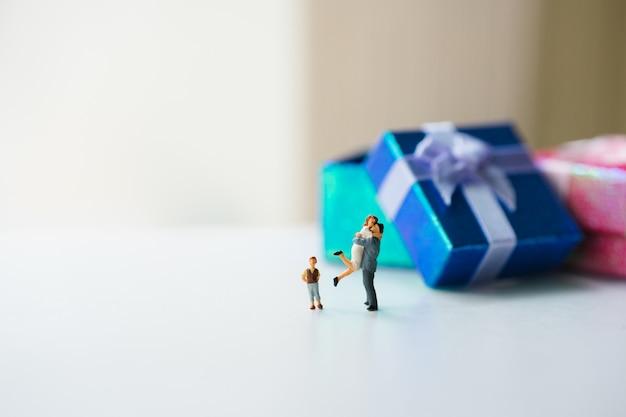 Miniaturleute, glückliche familie, die mit geschenkkasten unter verwendung als familienlebenkonzept steht