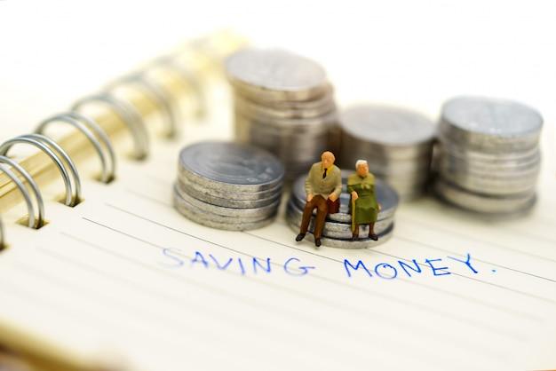 Miniaturleute, glückliches älteres paar, das auf münzenstapel mit text sitzt