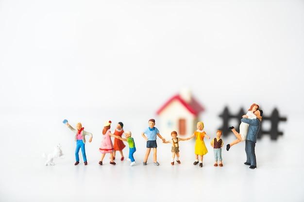 Miniaturleute, große familie, die zu hause unter verwendung als familienkonzept steht