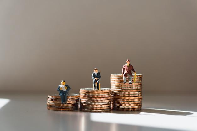 Miniaturleute, gruppe des mannes sitzend auf stapelmünzen unter verwendung