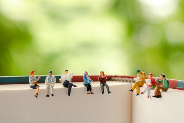 Miniaturleute: gruppe geschäftsleute, die auf einem buch sitzen.