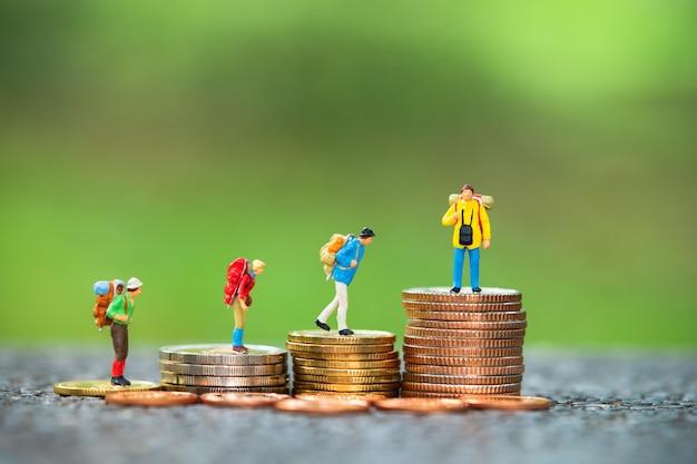 Miniaturleute, gruppe reisende, die auf stapelmünzen stehen