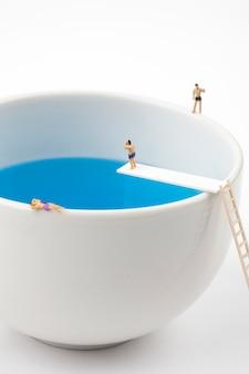 Miniaturleute im becherschalenswimmingpool
