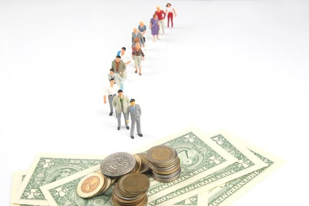 Miniaturleute in einer warteschlange für münzen und dollarscheine auf weißem hintergrund