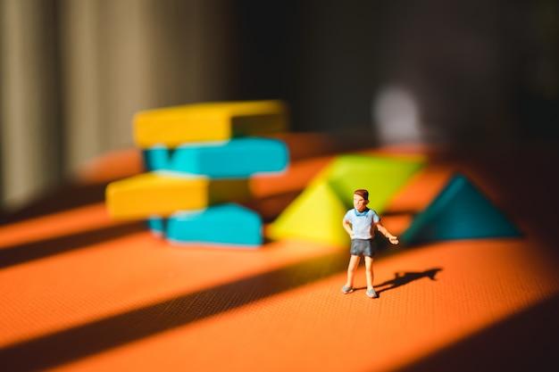 Miniaturleute, junge, der auf tangrampuzzlespielhintergrund unter verwendung als bildungsfähigkeitskonzept steht