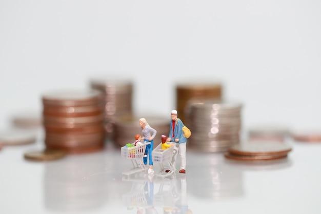 Miniaturleute: käufer, der neben geld, geschäft unter verwendung als hintergrund geht