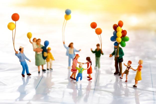 Miniaturleute: kinder, die mit ballon spielen.