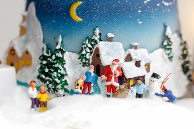 Miniaturleute: kinder, die spaß mit schneemann spielen.