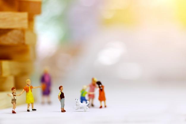 Miniaturleute, kinder und familie genießen mit hund, glückliches familientageskonzept.