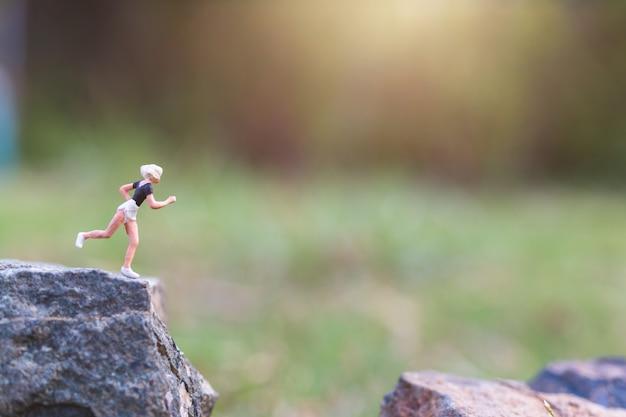 Miniaturleute: laufen auf felsenklippe mit naturhintergrund