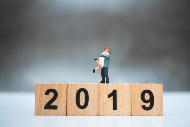 Miniaturleute, liebhaber, der auf holzblockjahr 2019 unter verwendung als familienkonzept steht
