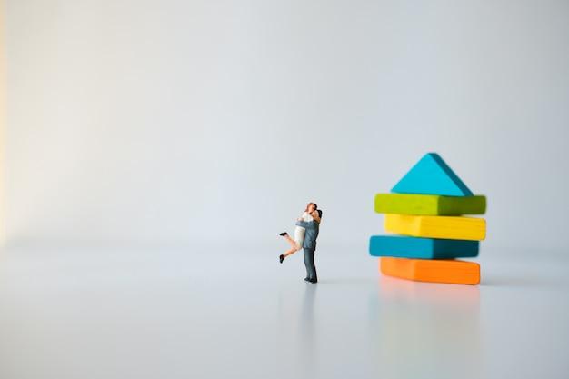 Miniaturleute, liebhaber, der mit tangrampuzzlespielhintergrund sich umarmt