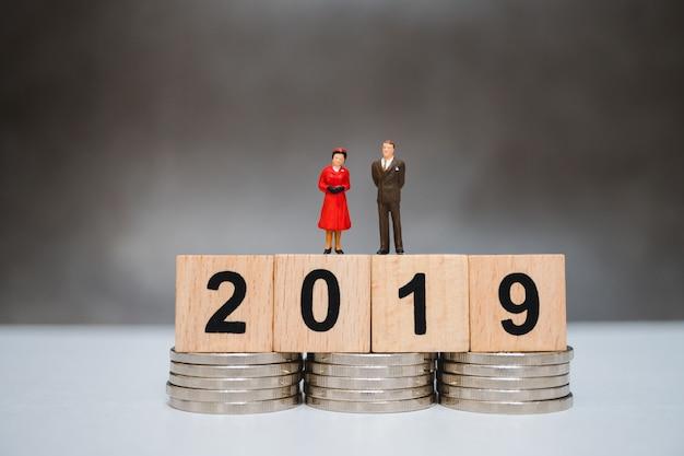 Miniaturleute, -mann und -frau, die auf hölzernem jahr 2019 stehen und stapelmünzen