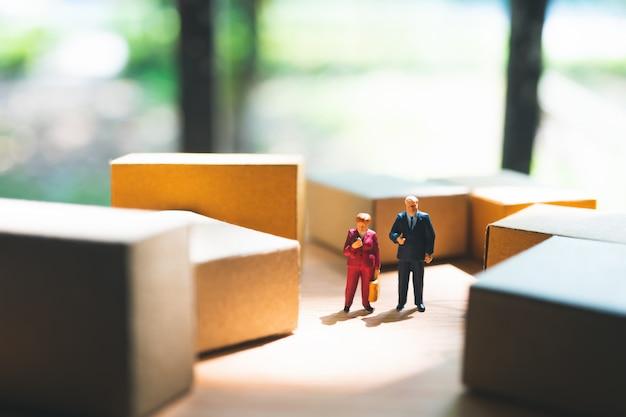 Miniaturleute, mann und frau, die mit kartonkästen stehen, verwenden als geschäfts- und logistikkonzept