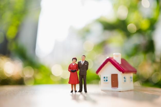 Miniaturleute, mann und frau, die mit minihaus auf dem grünen naturhintergrund unter verwendung als relatio stehen