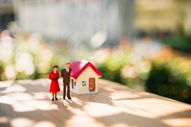 Miniaturleute, mann und frau, die mit minihaus auf grünem natur bokeh hintergrund unter verwendung als r stehen