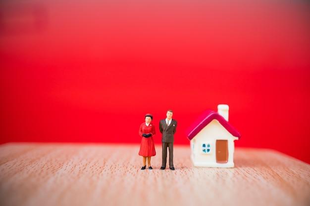 Miniaturleute, mann und frau, die mit minihaus auf rotem hintergrund unter verwendung als verhältnis und stehen