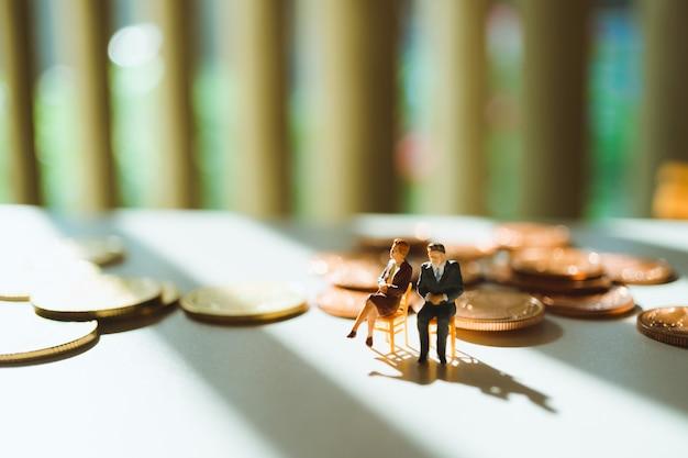 Miniaturleute, mann und frau, die mit stapel sitzen, prägt unter verwendung als geschäfts- und finanzkonzept