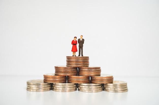 Miniaturleute, -mann und -frau, die mit stapelmünzen unter verwendung als geschäfts- und familienkonzept stehen