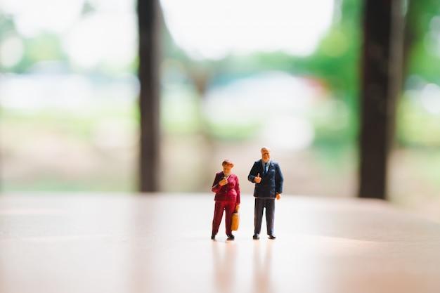 Miniaturleute, mann und frau, die unter verwendung als geschäfts- und familienkonzept im freien stehen