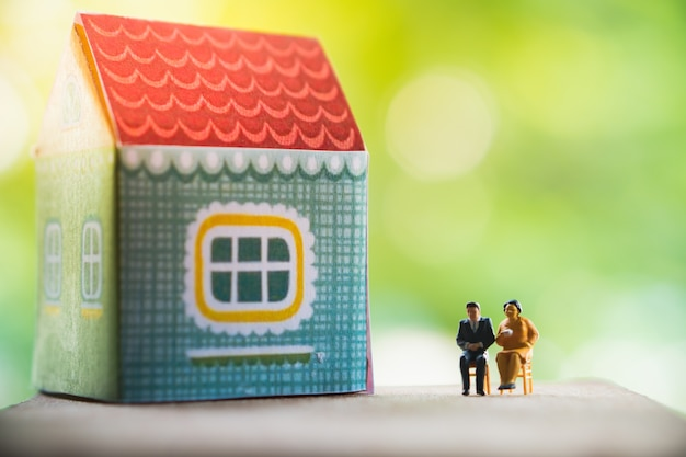 Miniaturleute, mann und frau, die vor haus sitzen