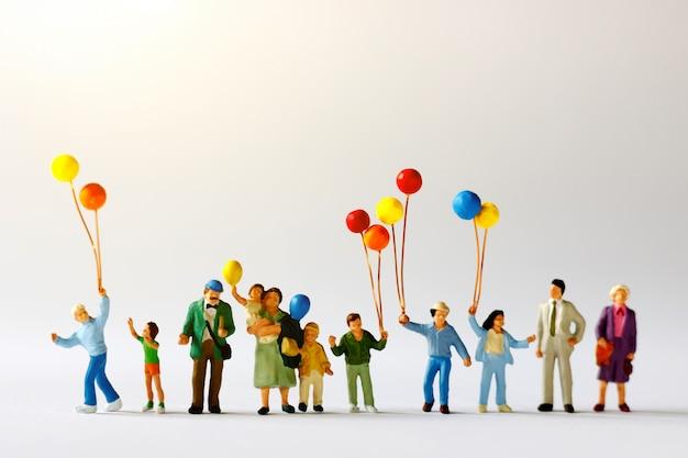 Miniaturleute mit der familie, die ballon auf der karte mit sonnenlicht, glückliches familientageskonzept hält.