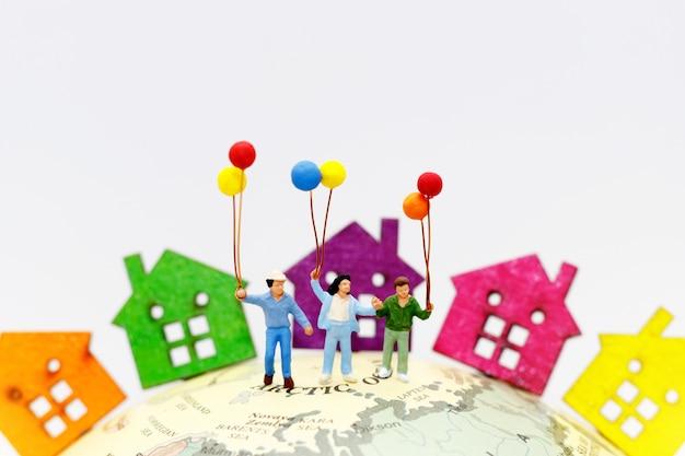 Miniaturleute mit der familie, die ballon mit häusern auf der kugel hält.
