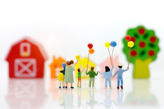 Miniaturleute mit der familie, die ballon mit häusern hält.