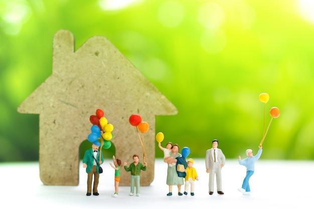 Miniaturleute mit der familie, die ballon mit haus hält.