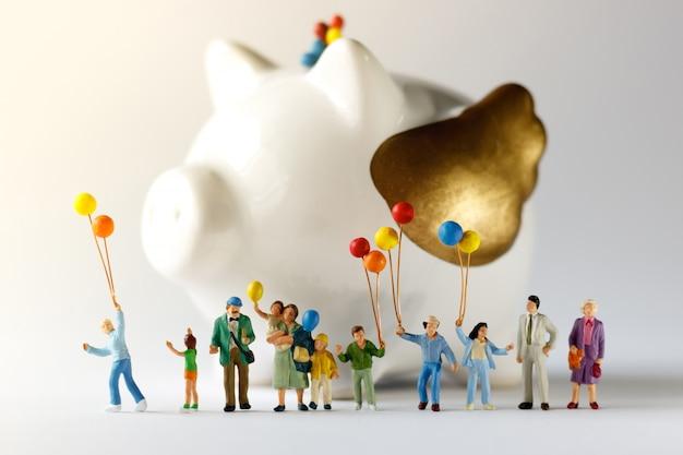 Miniaturleute mit der familie, die ballon mit sparschwein hält.