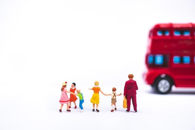 Miniaturleute, mutter und kinder, die den bus verwenden als familien- und bildungskonzept warten