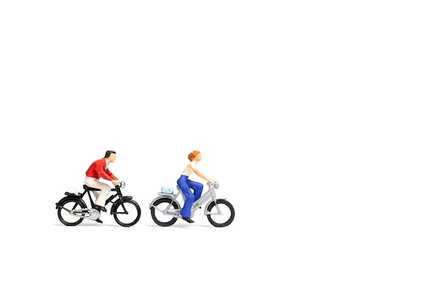Miniaturleute: paar fahren fahrrad auf weißem hintergrund
