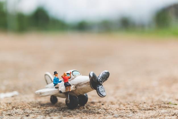Miniaturleute: paare, die auf dem flugzeug sitzen