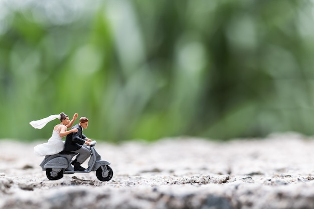 Miniaturleute: paare, die das motorrad reiten